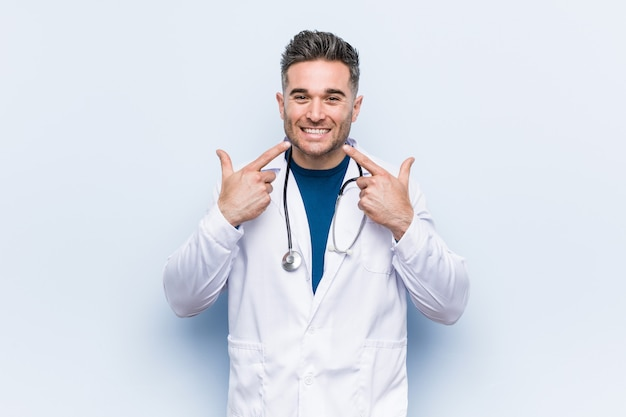 Young handsome doctor man smiles, pointing fingers at mouth.