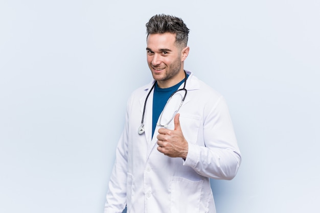 Young handsome doctor man smiling and raising thumb up