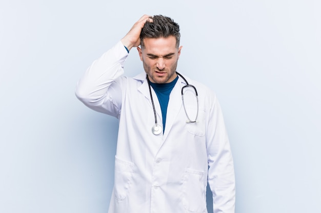 Young handsome doctor man tired and very sleepy keeping hand on head.