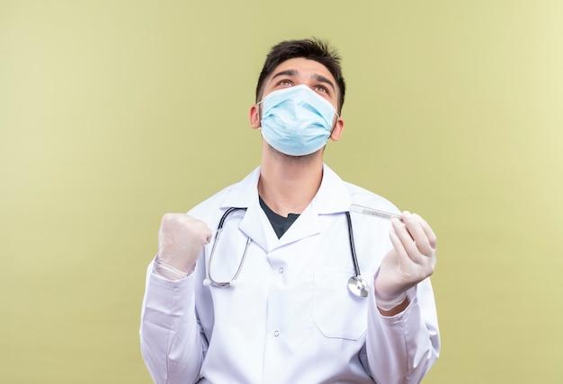 Giovane medico bello che indossa la maschera medica blu camice medico bianco guanti medici bianchi e uno stetoscopio felicemente tenendo il termometro contento con i risultati della temperatura in piedi sopra il cachi