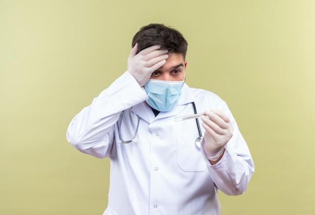 Giovane medico bello che indossa la maschera medica blu camice medico bianco guanti medici bianchi e uno stetoscopio spaventato che tiene il termometro in piedi sopra la parete cachi