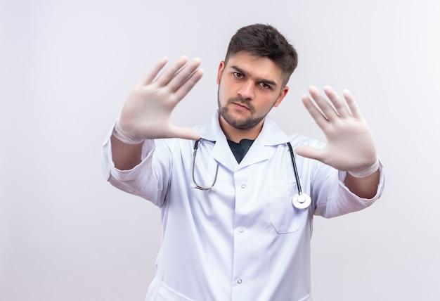 Молодой красивый врач в белом медицинском халате, белые медицинские перчатки и стетоскоп, сердито показывая знак остановки с руками, стоящими над белой стеной