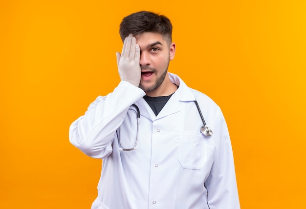 Молодой красивый врач в белом медицинском халате, белые медицинские перчатки и стетоскоп, закрывающий один глаз, стоящий над оранжевой стеной