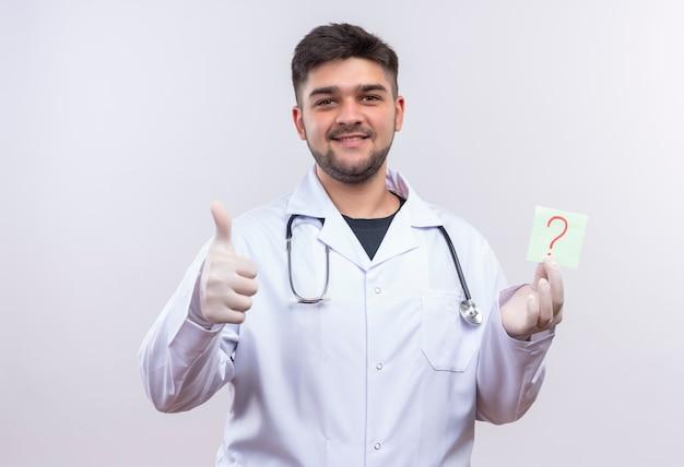 Молодой красивый врач в белом медицинском халате, белые медицинские перчатки и стетоскоп делает счастливые пальцы вверх, держа вопрос над белой стеной
