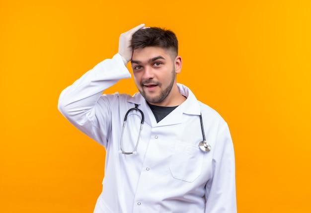 白い医療用ガウン白い医療用手袋と聴診器を身に着けている若いハンサムな医者は、オレンジ色の壁の上に立っている忘れられた顔で見ている手で彼の頭