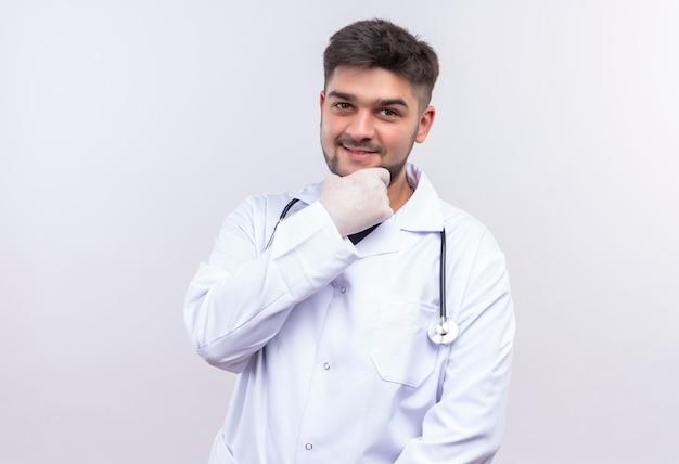 Молодой красивый врач в белом медицинском халате, белые медицинские перчатки и стетоскоп, держа челюсть рукой и улыбаясь
