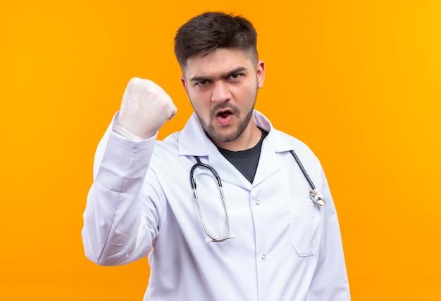 白い医療用ガウン白い医療用手袋と聴診器を身に着けている若いハンサムな医者は、オレンジ色の壁の上に立っている拳を見せて脅迫的に見えます