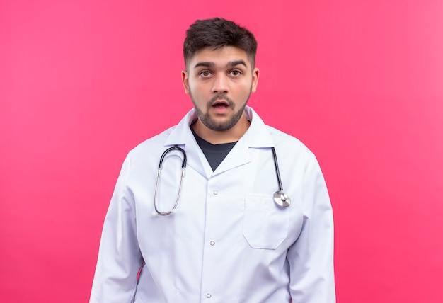 ピンクの壁の上に立って疲れて驚いて見える白い医療用ガウン白い医療用手袋と聴診器を身に着けている若いハンサムな医者