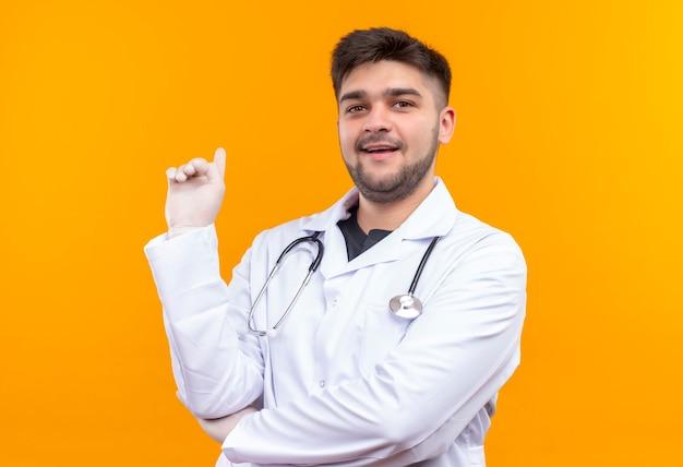 白い医療用ガウン白い医療用手袋と聴診器を身に着けている若いハンサムな医師は、オレンジ色の壁の上に立っている人差し指で後ろを向いて教える顔で見ています
