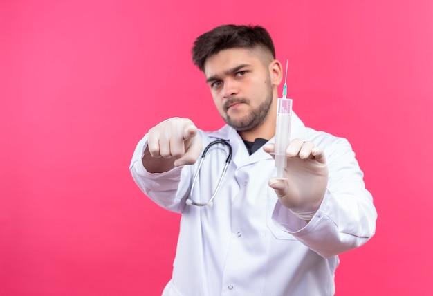 흰색 의료 가운 흰색 의료 장갑과 청진기를 입고 젊은 잘 생긴 의사, 분홍색 벽 위에 서있는 주사를 가리키고 들고