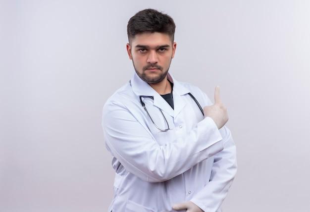 白い医療用ガウン白い医療用手袋と聴診器を身に着けている若いハンサムな医師は、白い壁の上に立っている人差し指で真剣に振り返って見ています