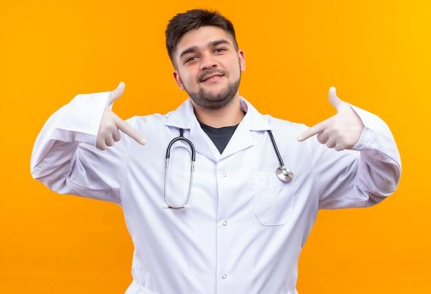 Молодой красивый врач в белом медицинском халате, белые медицинские перчатки и стетоскоп