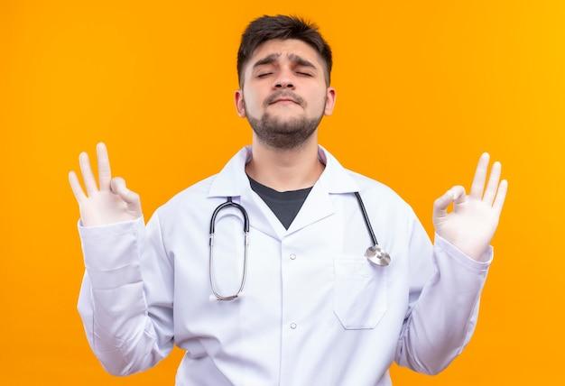 Giovane medico bello che porta i guanti medici bianchi dell'abito medico bianco e gli occhi di chiusura dello stetoscopio che fanno segno giusto con le mani che stanno sopra la parete arancione