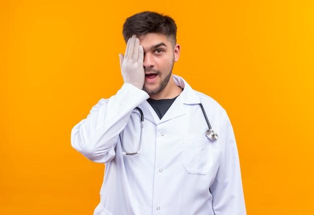 Giovane medico bello che porta guanti medici bianchi dell'abito medico bianco e stetoscopio che chiude un occhio che si leva in piedi sopra la parete arancione