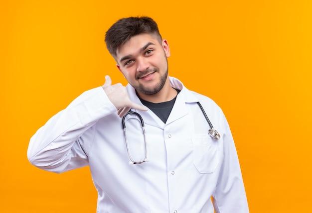 Giovane medico bello che porta i guanti medici bianchi dell'abito medico bianco e lo stetoscopio che fa mi chiamano segno che sta sopra la parete arancione