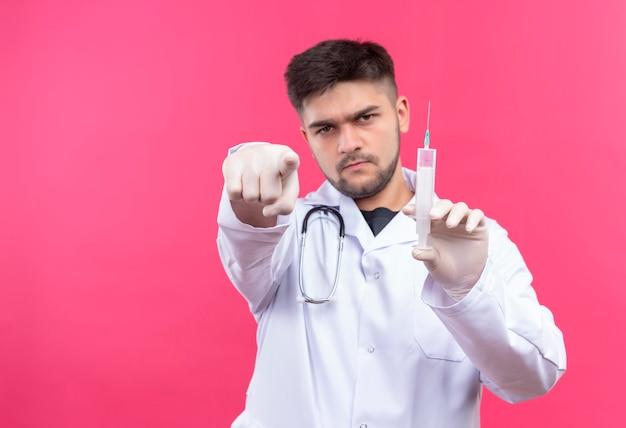 Giovane medico bello che porta guanti medici bianchi e stetoscopio bianchi dell'abito medico, indicando e tenendo l'iniezione che sta sopra la parete rosa