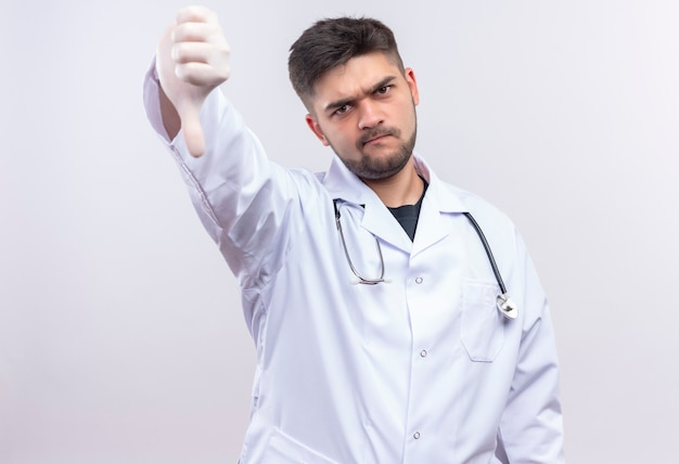 Young handsome doctor wearing white medical gown white medical gloves and stethoscope reproachfully doing bad thumbs down standing over white wall