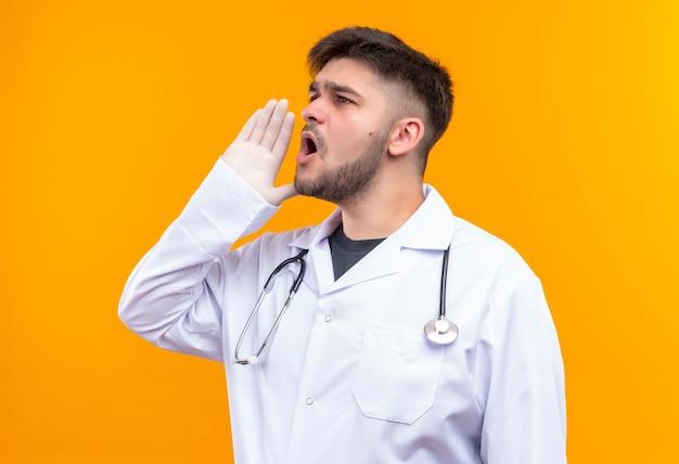 Giovane medico bello che indossa guanti medici bianchi dell'abito medico bianco e stetoscopio che grida dopo a qualcuno che sta sopra la parete arancione