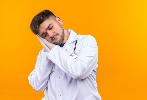 Young handsome doctor wearing white medical gown white medical gloves and stethoscope sleeping standing over orange wall