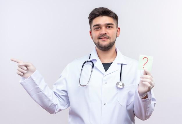 Giovane medico bello che porta i guanti medici bianchi dell'abito medico bianco e lo stetoscopio che sorridono tenendo il segno di domanda e che indica a destra che sta sopra il muro bianco