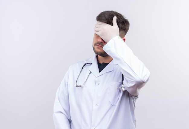 Young handsome doctor wearing white medical gown white medical gloves and stethoscope upset doing facepalm standing over white wall