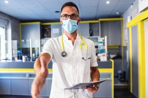 テスト結果のフォルダを保持し、患者の手に手を伸ばして彼と挨拶するフェイスマスクを持つ若いハンサムな医者。