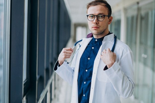 Young handsome doctor with stethoscope at clinic