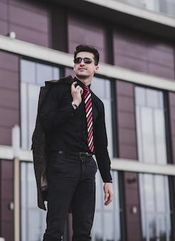 事務所ビルやホテルの近くのフォーマルな服装の若いハンサムな起業家