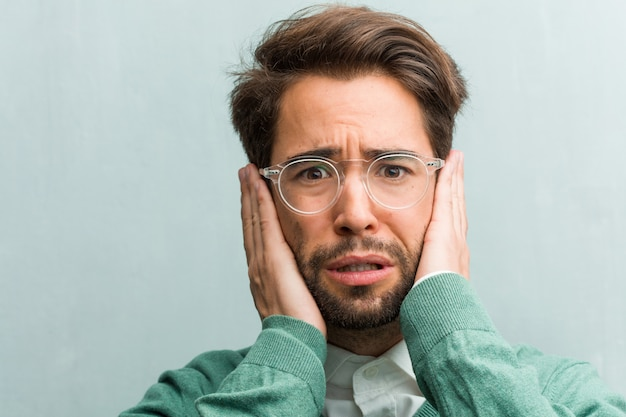 Young handsome entrepreneur man face closeup covering ears with hands