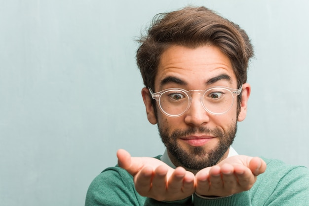 Young handsome entrepreneur man face closeup holding something with hands