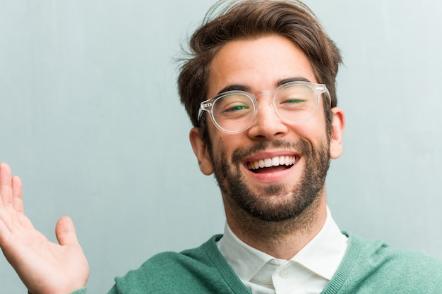 Young handsome entrepreneur man face closeup laughing and having fun, being relaxed and cheerful, feels confident and successful