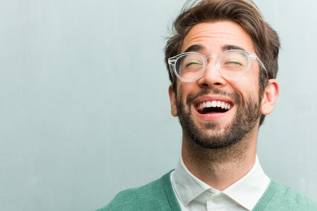 Young handsome entrepreneur man face closeup laughing and having fun, being relaxed and cheerful