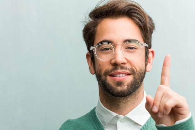 Young handsome entrepreneur man face closeup showing number one, symbol of counting