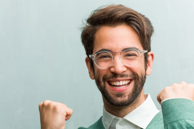 Young handsome entrepreneur man face closeup very happy and excited
