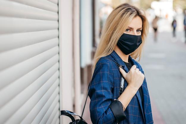 街を歩くコロナウイルスから身を守るために顔の汚染マスクのバックパックとサングラスの若いハンサムなファッションの女性