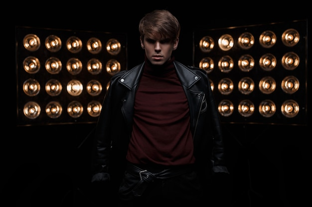 Young handsome fashionable man in a leather black jacket in burgundy golf in stylish pants posing in a dark studio against a background of bright electric vintage orange bulbs. cute guy. fashion.