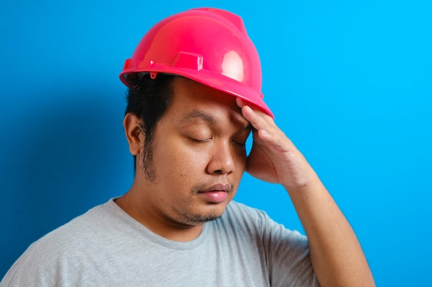 Young handsome fat asian worker man wearing grey t-shirt and security helmet suffering from headache desperate and stressed because pain and migraine. hands on head