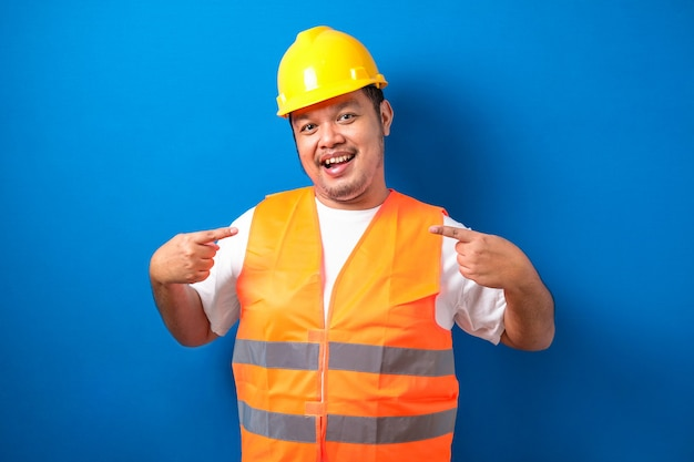 Young handsome fat asian worker man wearing orange vest and safety helmet looking confident