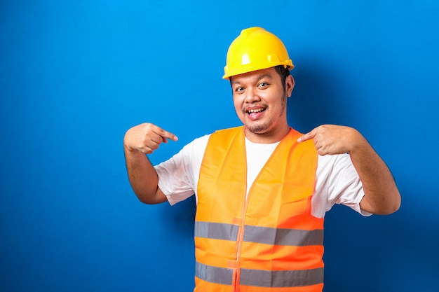Young handsome fat asian worker man wearing orange vest and safety helmet