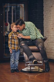 이발소에서 이발사를 기다리는 젊고 잘생긴 아버지와 그의 작고 세련된 아들