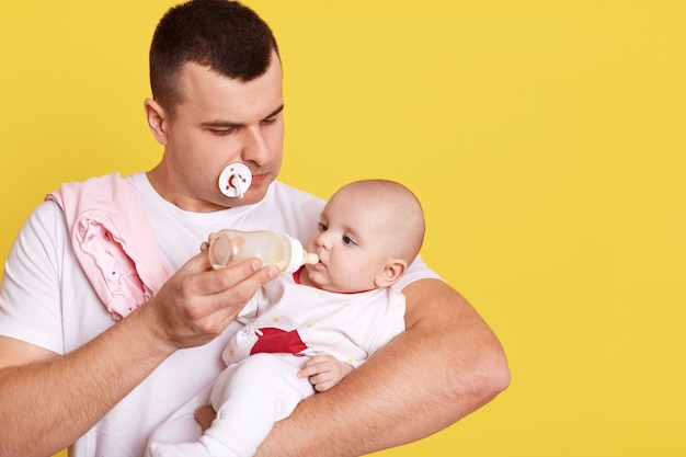 Молодой красивый отец кормит своего новорожденного сына молоком из бутылочки для кормления
