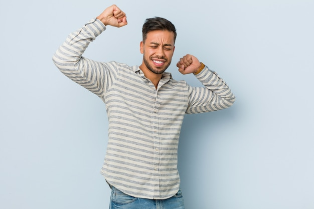 Young handsome filipino man celebrating a special day, jumps and raise arms with energy.