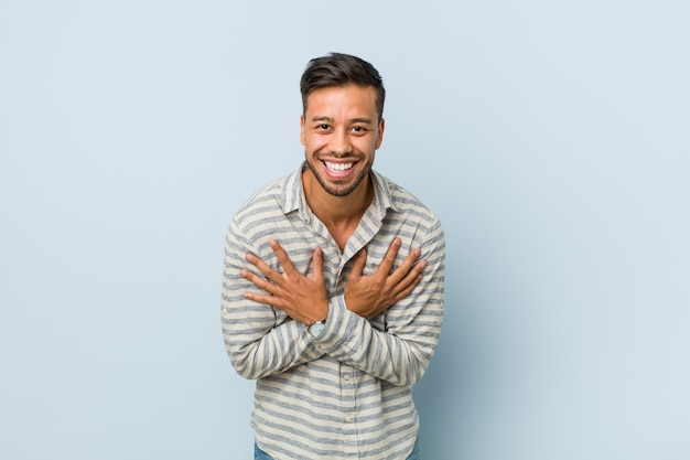 Young handsome filipino man laughs happily and has fun keeping hands on stomach.
