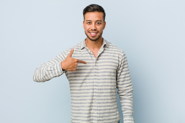 Young handsome filipino man person pointing by hand to a shirt copyspace, proud and confident