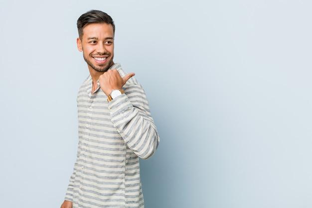 若いハンサムなフィリピン人男性が親指の指で離れて、笑って屈託のないポイントします。