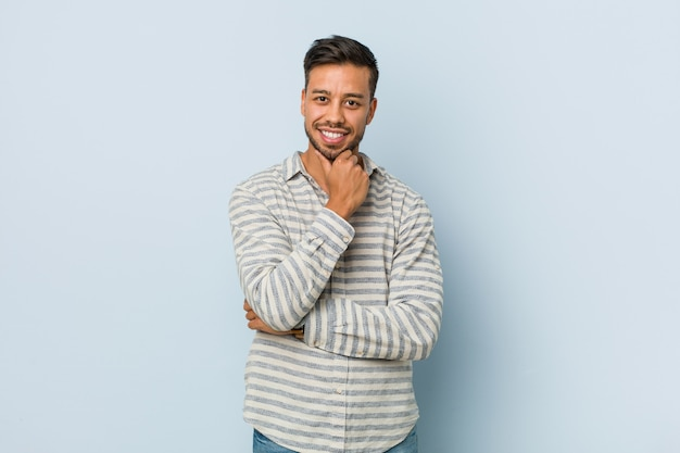 Young handsome filipino man smiling happy and confident, touching chin with hand.