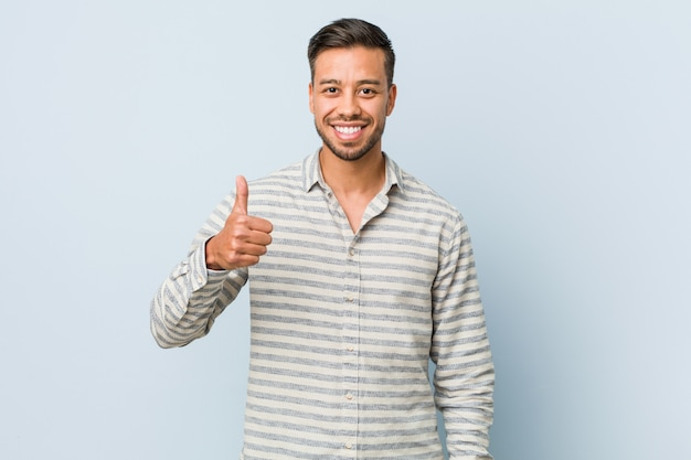 Young handsome filipino man smiling and raising thumb up