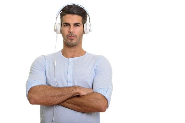 Молодой красивый здоровый персидский мужчина слушает музыку с крестом на руках