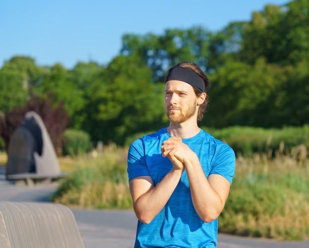 Молодой красивый спортсмен в спортивной одежде смотрит в сторону, разогревая руки и запястья