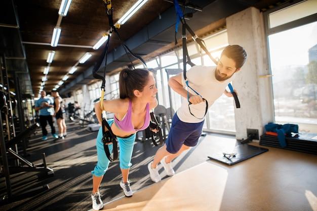 ジムで運動しながらいちゃつく若いハンサムなフィットネスカップル。